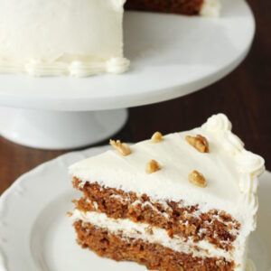 A carrot cake sits on a white cake pedestal. The cake is frosted with fluffy cream cheese frosting and decorated with a few walnuts. A wedge of cake sits next to the stand ready to eat.