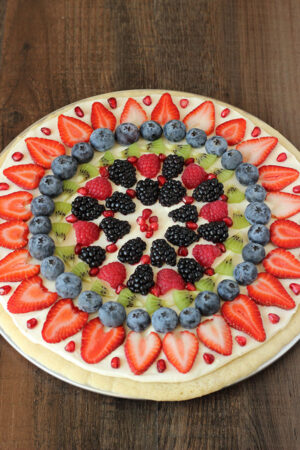 A fruit pizza made from a no chill sugar cookie crust, cream cheese frosting, and fruit. It is decorated with pomegranates, blackberries, raspberries, kiwi, blueberries, and sliced strawberries.