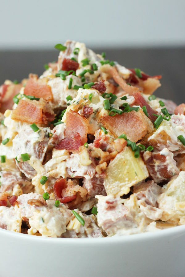 A big white bowl of loaded potato salad. The salad is full of chunks of sausage and pieces of bacon and covered in chives.