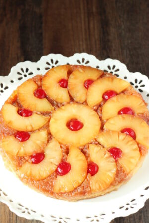 A beautiful pineapple upside down cake is displayed on a white cake stand. The pineapple is cut into half circles and arranged like a pinwheel around a center ring of pineapple. Cherries sit inside each ring or half ring.