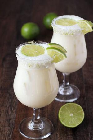 Tall refreshing glasses of Brazilian Lemonade garnished with limes.