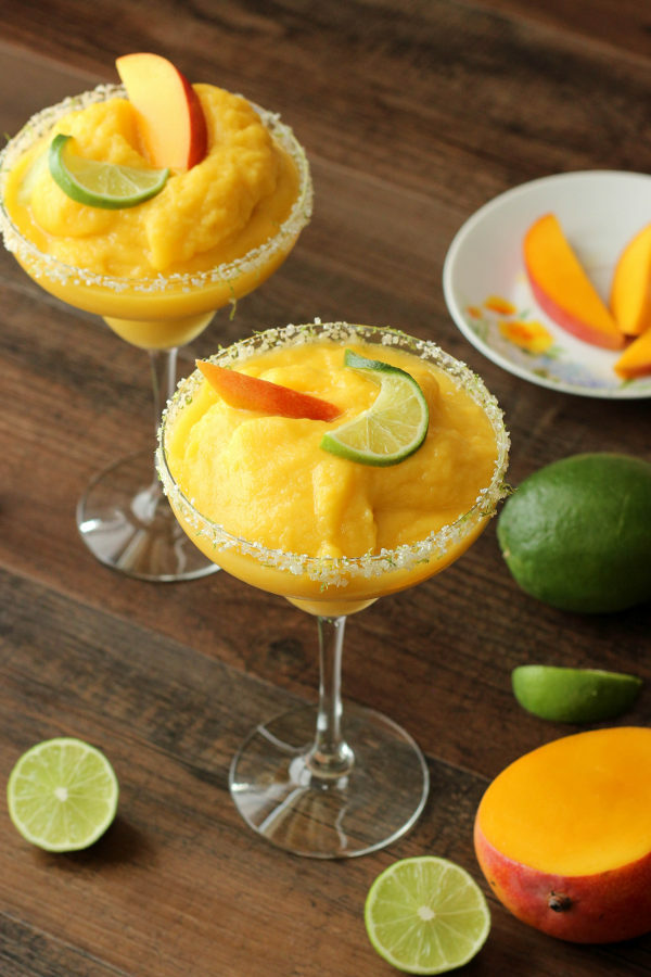 These frosty margarita glasses are full of frozen mango margarita and garnished with fresh mango and lime.