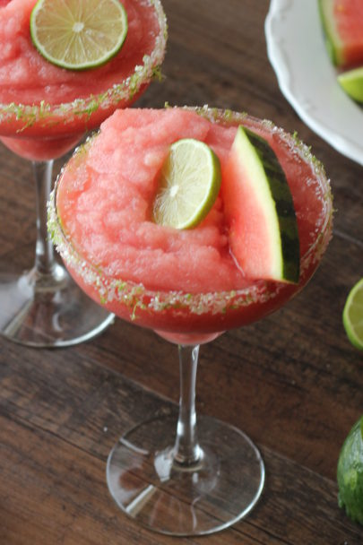 a big chilly glass of frozen watermelon margarita garnished with lime and a watermelon wedge