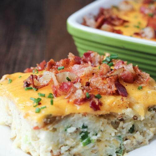 A big slice of loaded twice baked potato casserole sits on a white plate. It is covered in cheese, bacon and chives.