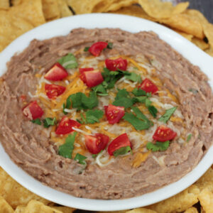 These creamy, flavorful refried beans were made in the instant pot without soaking! They are in a white bowl garnished with tomatoes, cilantro, and cheese. There are chips around the bowl.