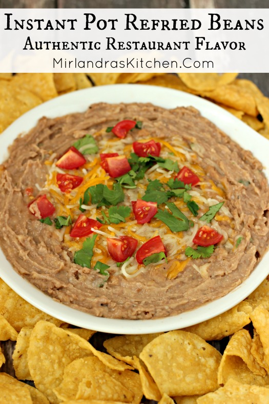 A bowl of refried beans is surrounded by chips and garnished with chunks of tomatoes, cilantro and a sprinkling of cheese.