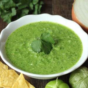 A beautiful bowl of bright green salsa verde sauce sits on the table. The sauce is garnished with a cilantro leaf and surrounded by tomatillos, chips, cilantro, and a cut onion.