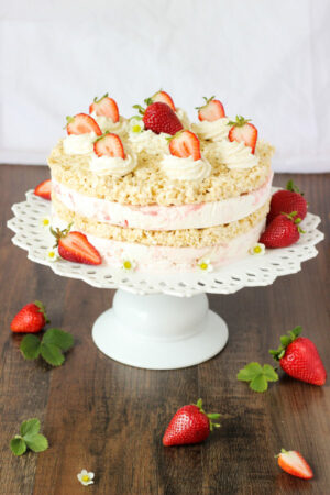 This strawberry ice cream sandwich cake is made from layers of rice crispy treats and strawberry cheesecake ice cream. The cake is decorated with swirls of whipped cream and fresh strawberries.