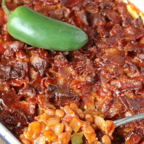 A white and blue pan is full of baked beans. The beans are covered in chopped bacon and the dish has a jalapeno on top.