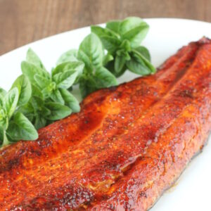 A white platter with a salmon filet on it. The salmon is seasoned with a brown sugar glaze and garnished with some basil.
