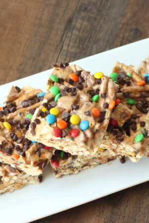 A white platter is sitting on a wooden table. The platter is full of marshmallow treat bar squares. You can see rice chex and pretzels in the bars. The tops are sprinkled with mini m and ms and mini chocolate chips.