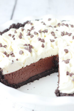 A beautiful chocolate cream pie is in a white pie plate. There is one slice removed so you can see the chocolate cookie crust, the rich chocolate filling, and swirls of whipped cream on top. There are mini chocolate chips scattered over the pie.