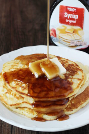 A plate of pancakes is covered in rich syrup that has been modified to taste homemade. You can see the store bought bottle of syrup in the background.
