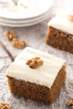 Squares of sweet, spicy pumpkin cake sit ready to eat. The cake is frosted with cream cheese frosting and decorated with walnuts.