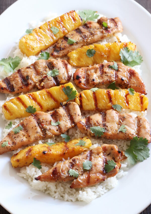 A white platter with a bed of rice. There are strips of grilled chicken breast and strips of grilled pineapple on the rice. The dish is garnished with cilantro leaves.