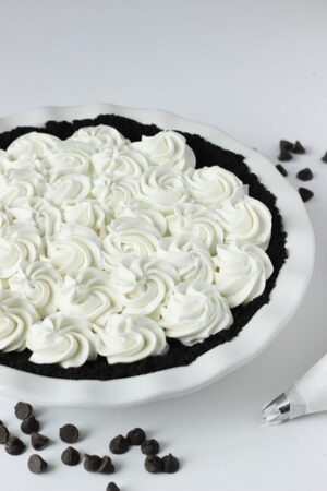 This chocolate cream pie is decorated with homemade whipped cream. The cream is piped on with lovely swirls.