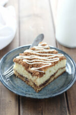 A big square of sour cream coffee cake sits on a blue pottery plate. There is a fork and a glass of milk next to it. The cake has visible layers of cinnamon sugar and a drizzle of vanilla icing.