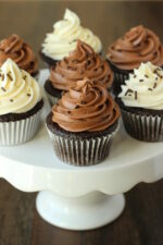 A white cake stand has seven chocolate cupcakes on it. Some cupcakes are frosted with chocolate frosting and some with vanilla buttercream. They all have chocolate sprinkles.