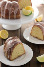 a 70up bundt cake sits on a white cake stand with a slice of lime and a slice of lemon. The cake is glazed with 7 up glaze. Two white plates sit on the table each with a big slice ready to go.