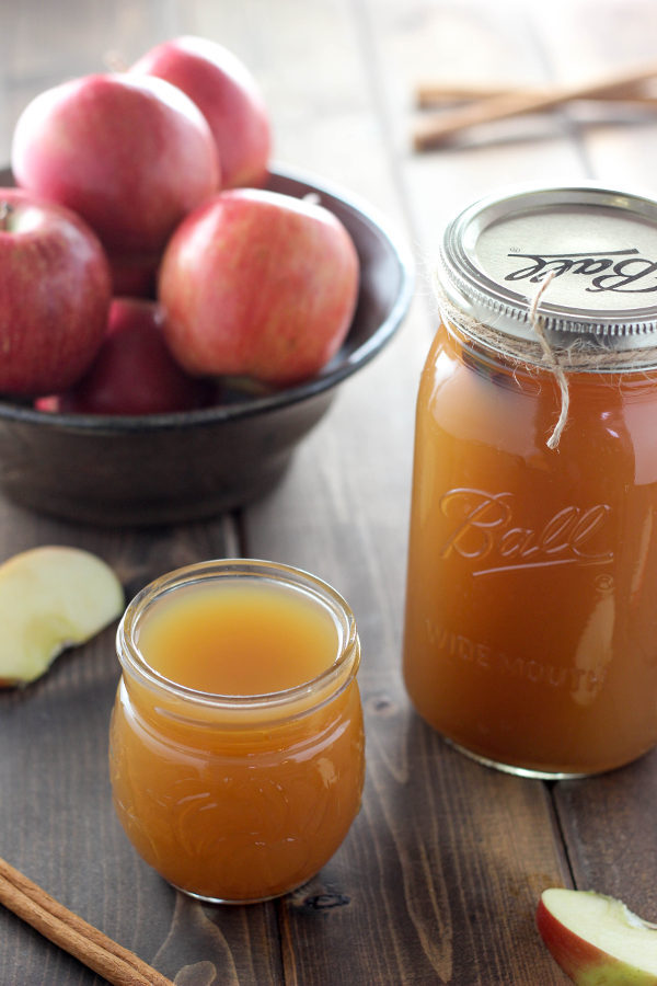 A quart mason jar full of apple pie moonshine sits on a wooden table next to a drinking glass of moonshine and a bowl of apples.