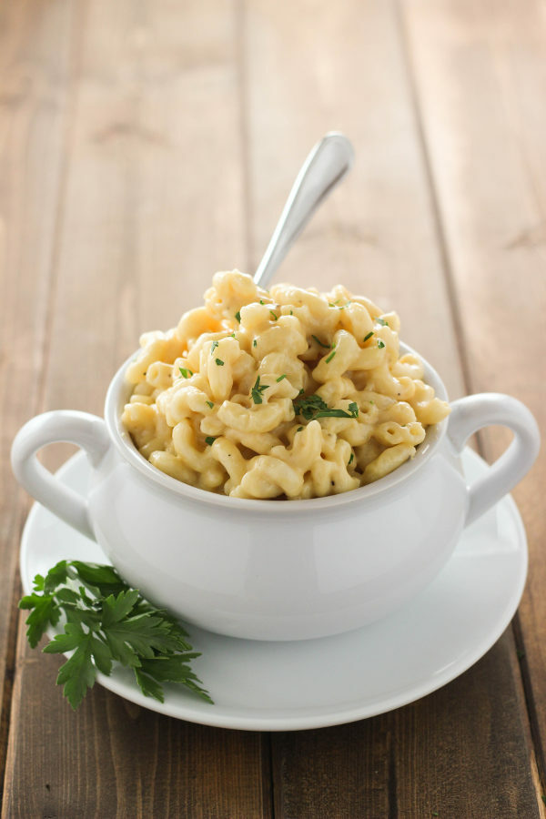 A white bowl is full of saucy, instant pot mac and cheese. The bowl is on a white plate garnished with a sprig of parsley and has a fork sticking out of it.