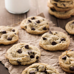 Delicious chocolate chip cookies are arranged on paper on a table. A stack of cookies and glass of milk are in the background.
