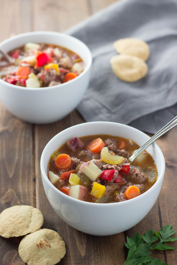 Two hearty bowls of delicious hamburger soup sit on a table with crackers and a gray napkin. You can see big chunks of potato, carrots, and hambuger.