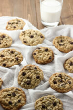 A batch of fresh chewy oatmeal chocolate chip cookies are laid out on a white cloth with a glass of milk.