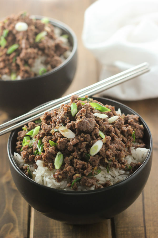 A black bowl is full of rice and then topped with savory Korean ground beef. It is garnished with green onions.