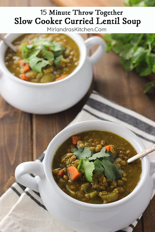 Two bowls of curried lentil soup sit on a wooden table. They are garnished with cilantro.