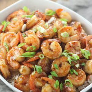 A large white serving bowl is full of shrimp in a golden honey garlic sauce. You can just see some rice under the shrimp and a sprinkling of green onion on top.