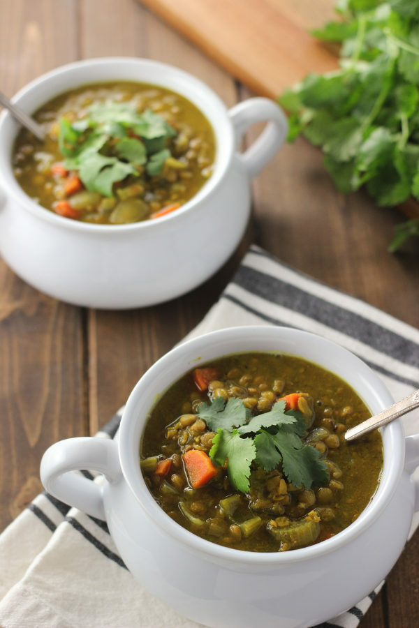 Two white bowls full of curried lentil soup are sitting on a wooden table. Each bowl has mug handles. The soup is garnished with fresh cilantro. You can see carrots and lentils in the yellow-brown lentil soup.