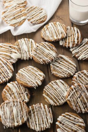 Soft ginger cookies with icing drizzled on them are arranged over a wooden table. There is a glass of milk in the background.
