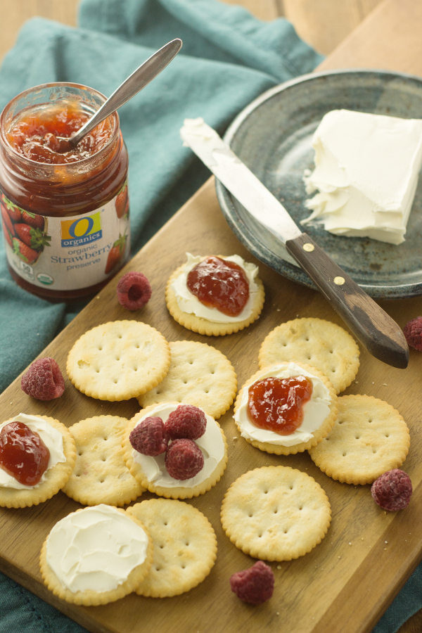 Ritz crackers on a cutting board. You an see a pot of jam and a plate with cream cheese. The crackers have cream cheese, jam and raspberries on them.