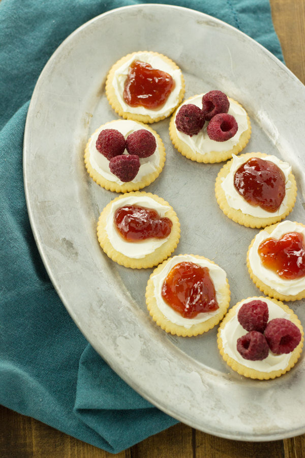 A silver oval platter has crackers on it. The crackers have cream cheese, jam, and raspberries as toppings.