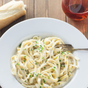 White bowl plate of pasta with 15 minute alfredo sauce from scratch. There is a loaf of french bread on the table and a glass of wine.
