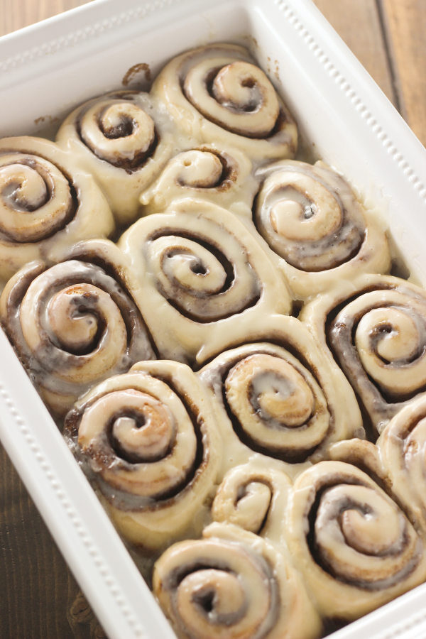 A large white baking dish full of cinnamon rolls slathered in glaze. You can see lots of cinnamon and plenty of sticky glaze.