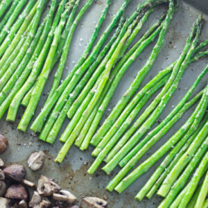 A baking sheet is covered with tender green spears of roasted asparagus and quartered mushrooms.