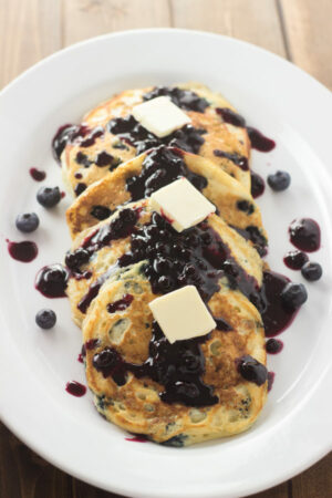 An oval platter is covered in beautiful wild blueberry pancakes. The pancakes have blueberry syrup and pats of butter on them.