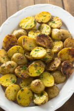 A large white platter of yellow baby potatoes. These potatoes have been sliced in half and oven roasted with garlic and Parmesan. They are finished with butter.