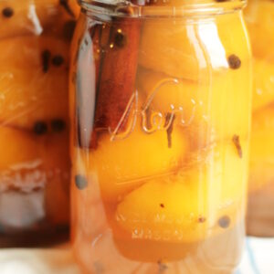 Three mason jars full of peach halves sit on the counter after canning. Each jar is studded with whole spices such as cinnamon, allspice, and cloves. The jars are sitting on a blue and white striped towel to cool.