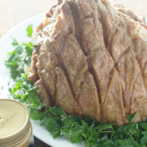 A large diamond cut ham sits on a platter of parsley. The ham has been glazed in cookie butter.