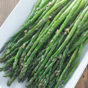 A white platter of tender spears of green asparagus sautéed in garlic butter.