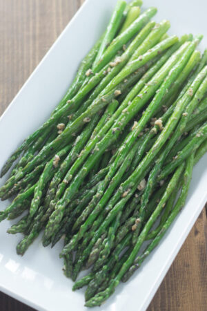 A white platter of tender spears of green asparagus sautéed in garlic butter.