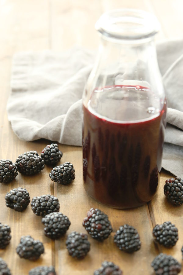 A clear glass bottle of blackberry syrup sits on a wooden table surrounded by fresh blackberries. There is a gray towel in the background.