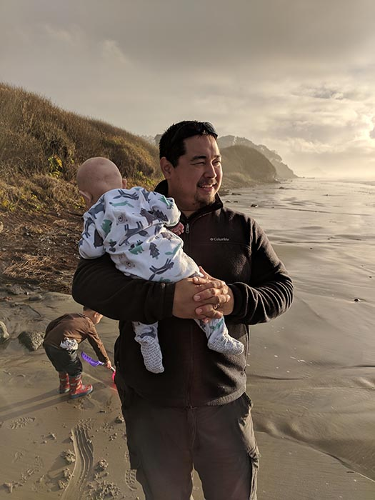 Baby Ella in the Dad's arms on the beach at the Oregon Coast.  Jack is digging in the sand in the background.