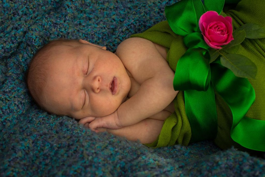 Ella on a blanket wrapped in a green scarf with a green bow and pink rose.