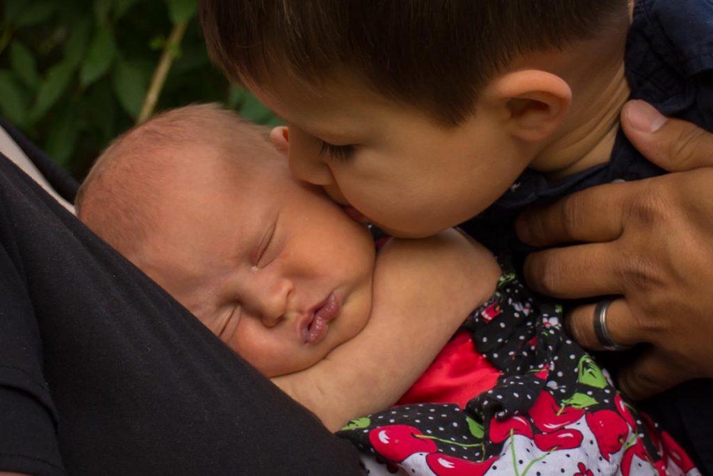 Jack kissing newborn Ella who is asleep on her mom.