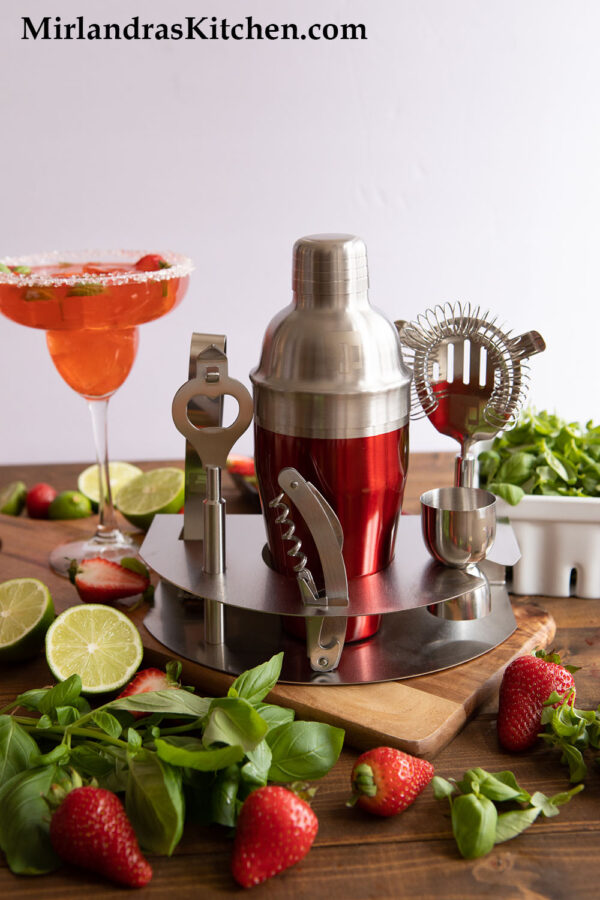 Red and silver cocktail shaker set with a strawberry margarita, basil, basil microgreens, limes and strawberries.