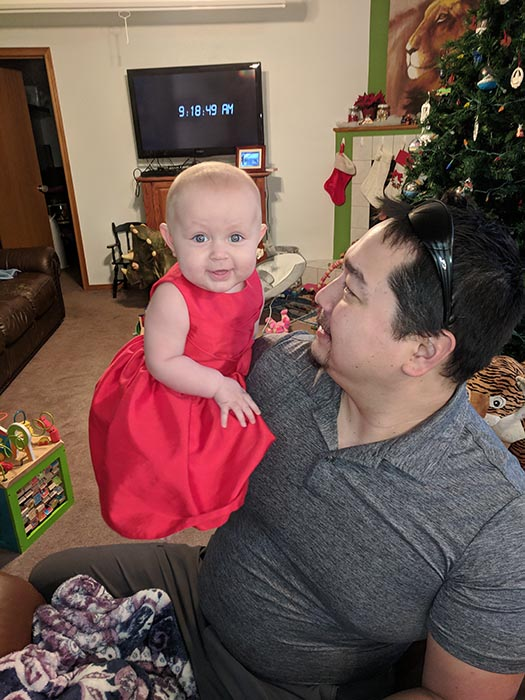 Baby Ella in her Christmas dress in the living room Dad is looking at her and holding her up.